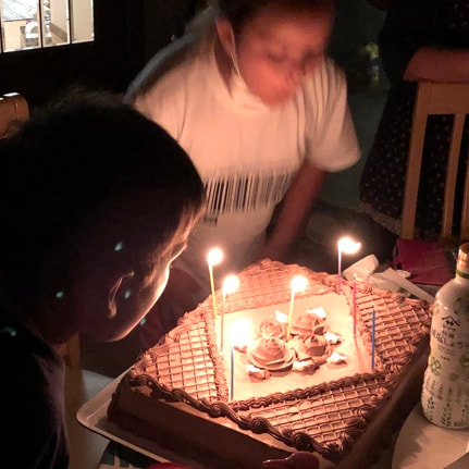 Two children blowing out the candles on a huge chocolate birthday cake.